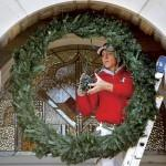 Terry Blevins Winds Second String Lights Around Wreath While